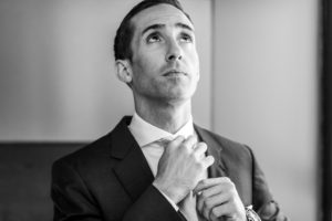 Anthony fixes his tie to prepare for his Sunday wedding